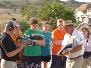 Filmmaker Bob Giguere records students on expedition learning about Mayan use of astronomy and architecture from a tour guide at Tulum, Mexico.
