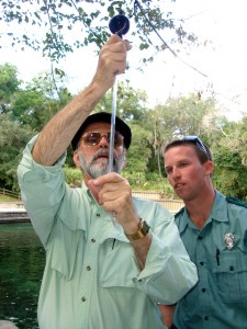 Aaron performing water quality tests while park ranger looks on.